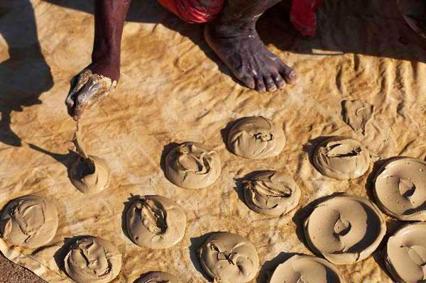 Масаи готовят лепешки из глины.